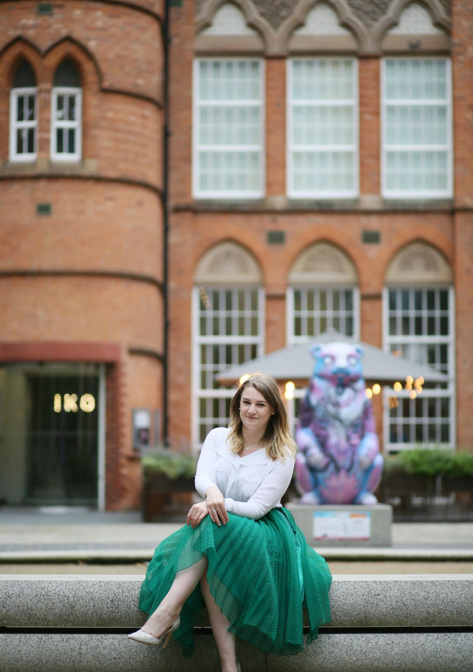 An image of Charlotte sitting outside Icon Gallery, Birmingham