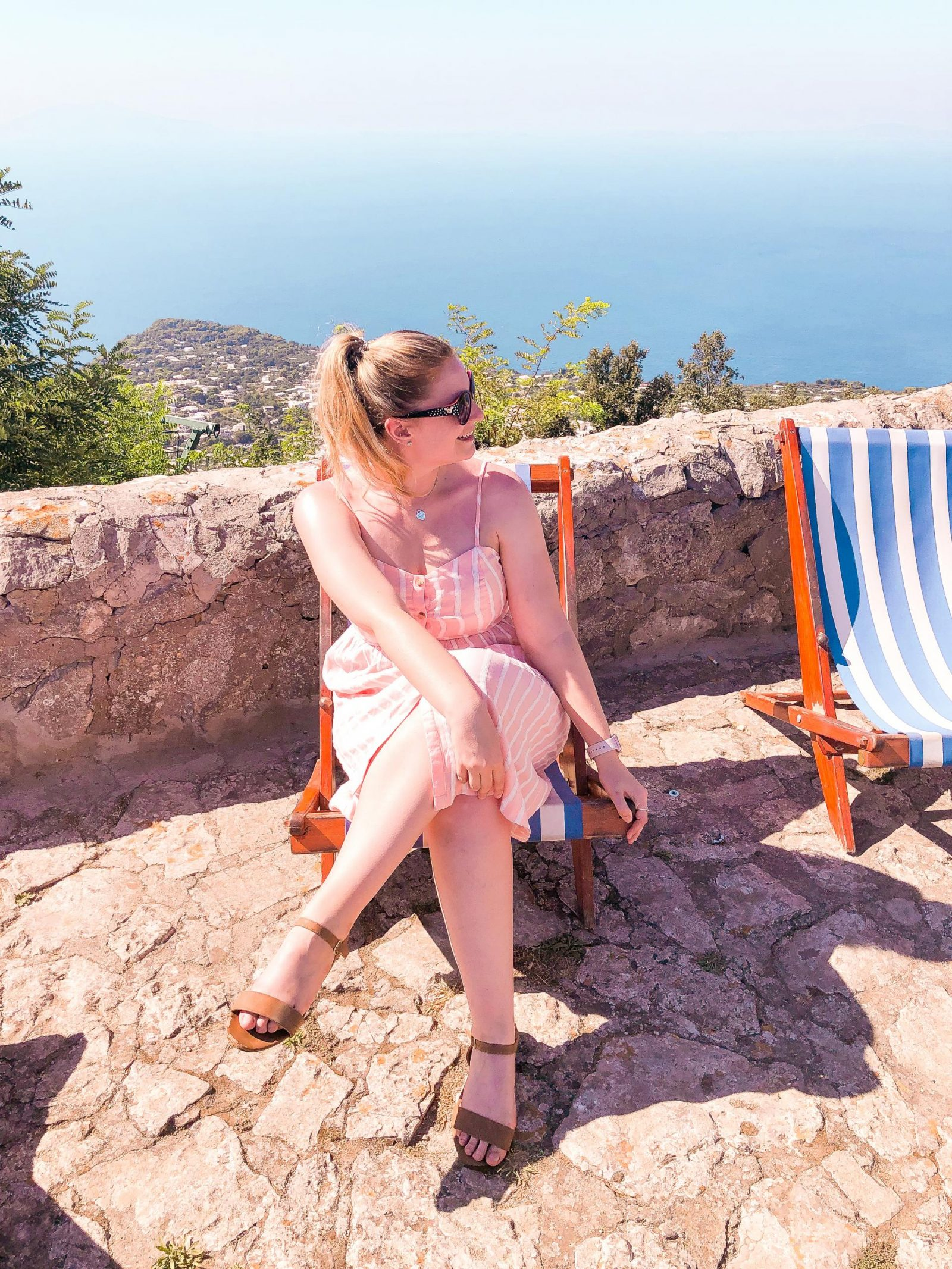 Charlotte Ruff sitting on a deck chair at the top of Capri, on a day trip from Sorrento.